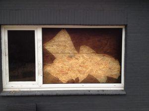 Zerstörte und abgesicherte Fensterscheibe nach einem Polizeieinsatz